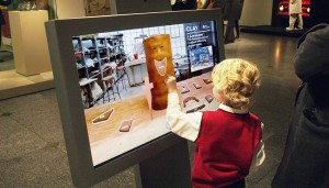 A child building a sculpture on one of the 'Lens' interactive units