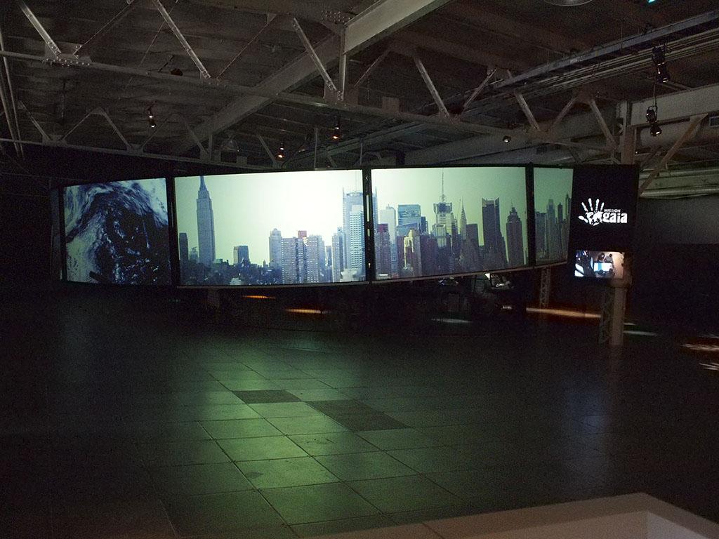 Espace industriel sombre comportant une large série d'écrans où sont projetés des paysages urbains