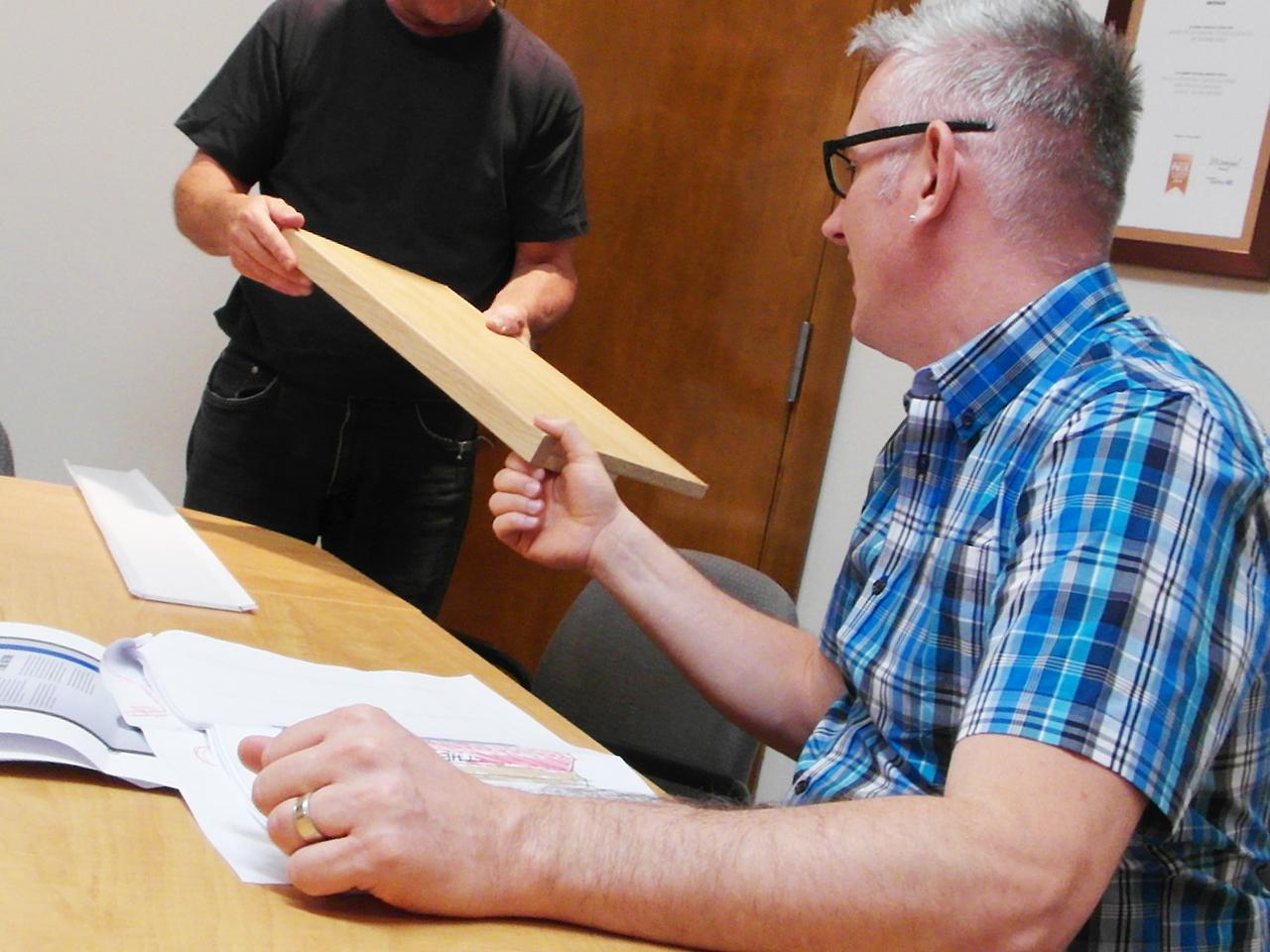 Homme scrutant un morceau de bois