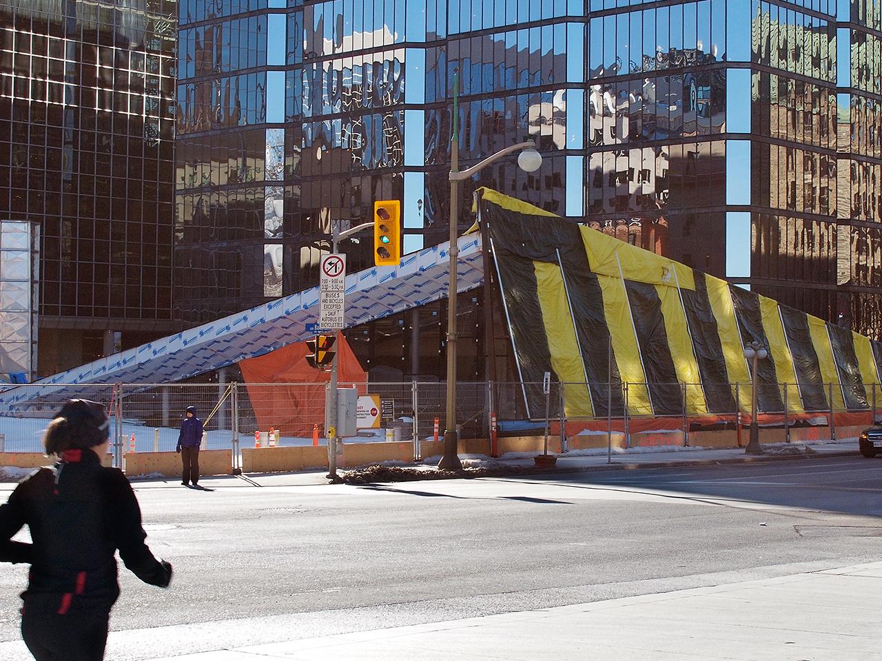 structure vitrée avec toit en angle et bâches jaunes