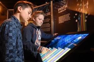 deux garçons manipulant un écran tactile