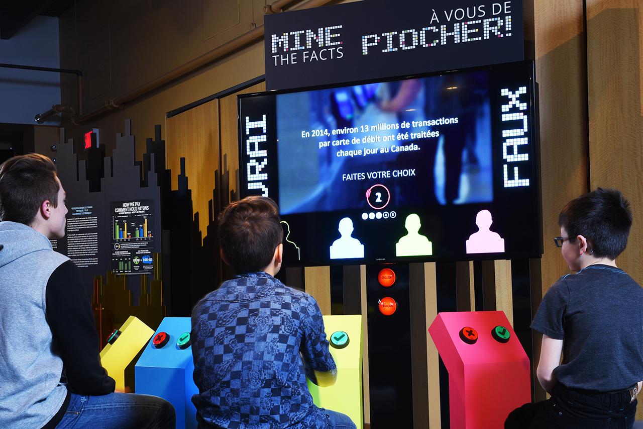 groupe d'enfants assis devant un grand panneau numérique