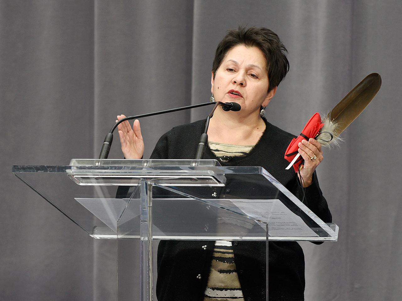 une femme parlant avec une plume à la main