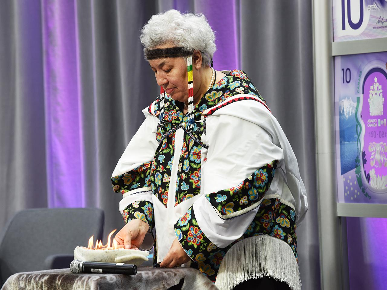 une femme allumant une lampe inuite