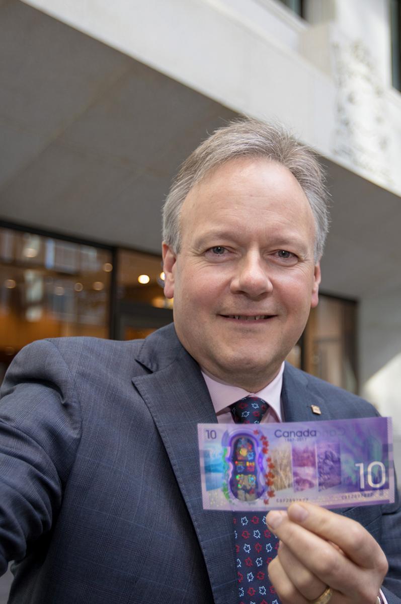 Stephen S. Poloz tenant un nouveau billet de 10 $