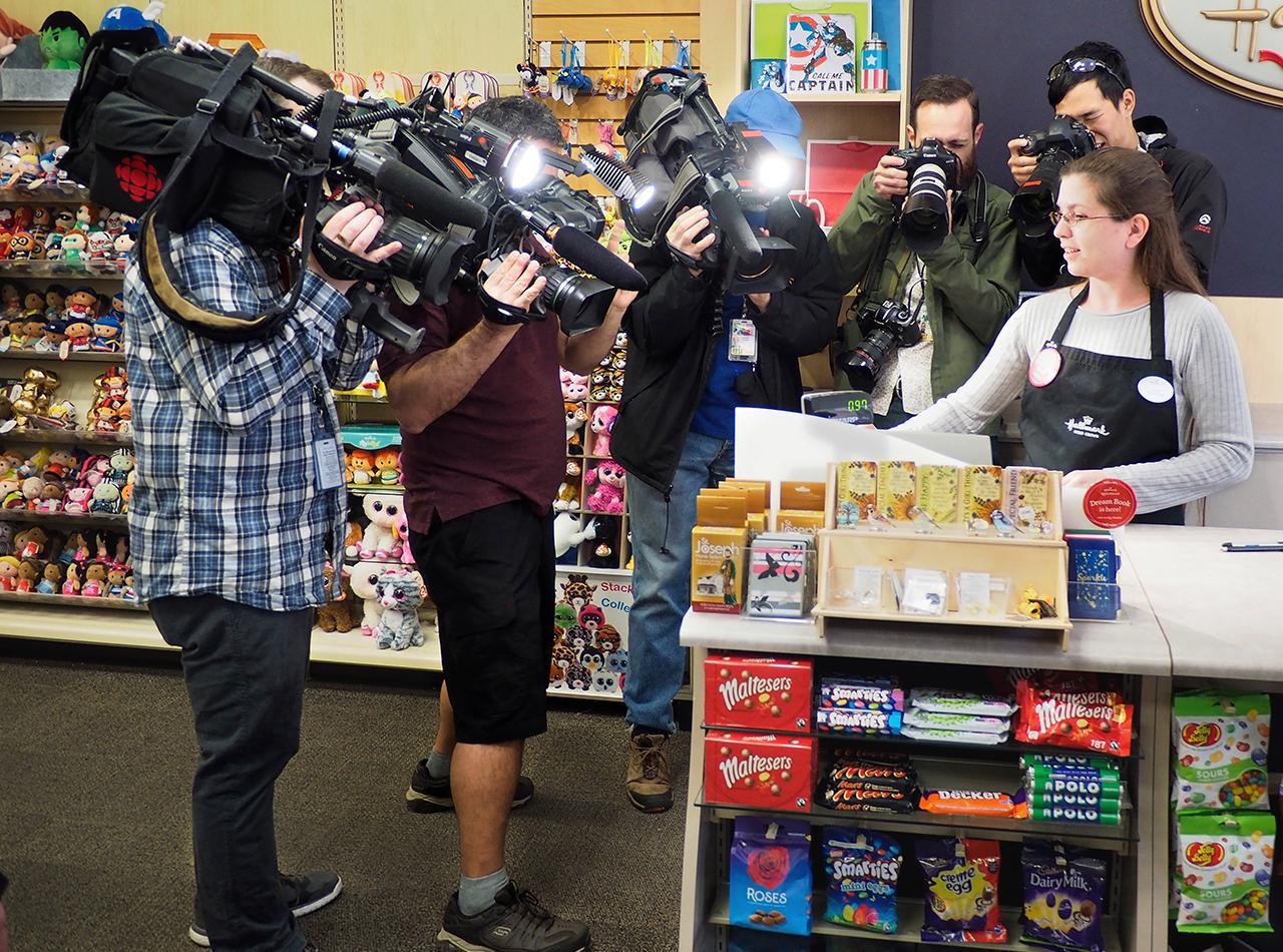des photographes et des caméramans massés autour d'une caissière