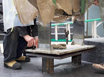 un ouvrier insère des boulons dans une plaque de métal