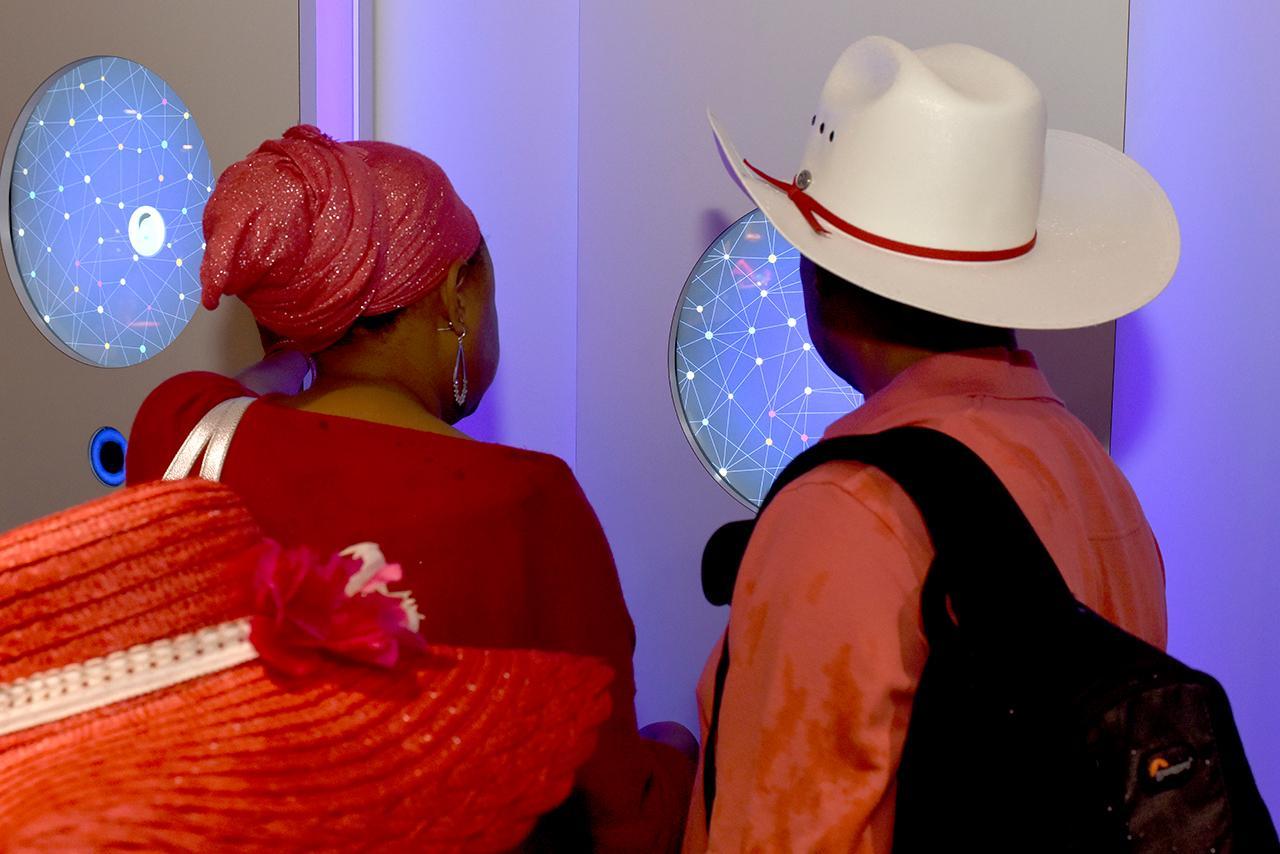 deux visiteurs devant un écran tactile