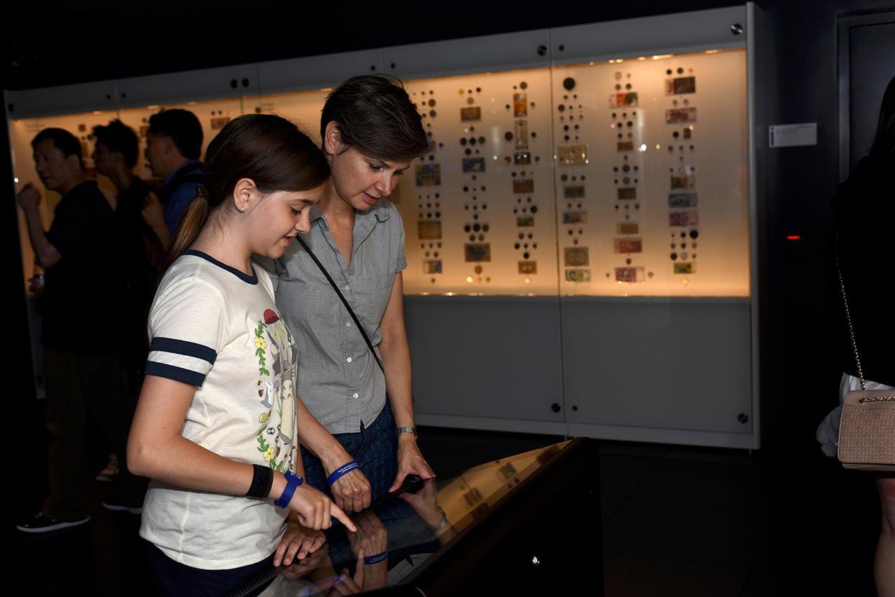 femme et jeune fille devant un écran tactile