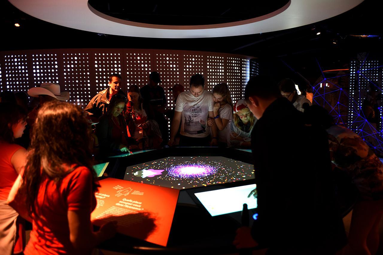 foule rassemblée autour d'une grande table numérique