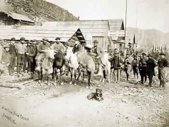 chevaux devant des bâtiments en bois