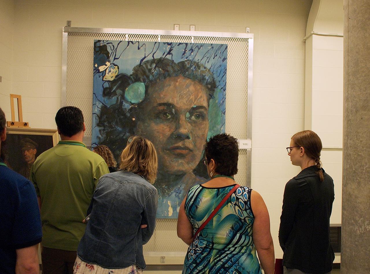personnes qui regardent des peintures mises en réserve