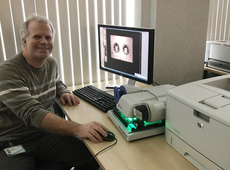 un homme devant un lecteur de microfilms