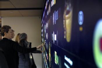 visiteurs qui interagissent avec un écran géant