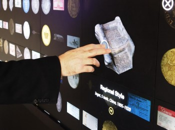 main touchant à l'écran une image d'artéfact