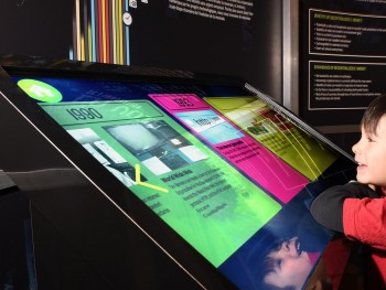 garçon devant un panneau tactile coloré