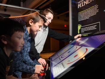 trois garçons devant un écran de jeu vidéo