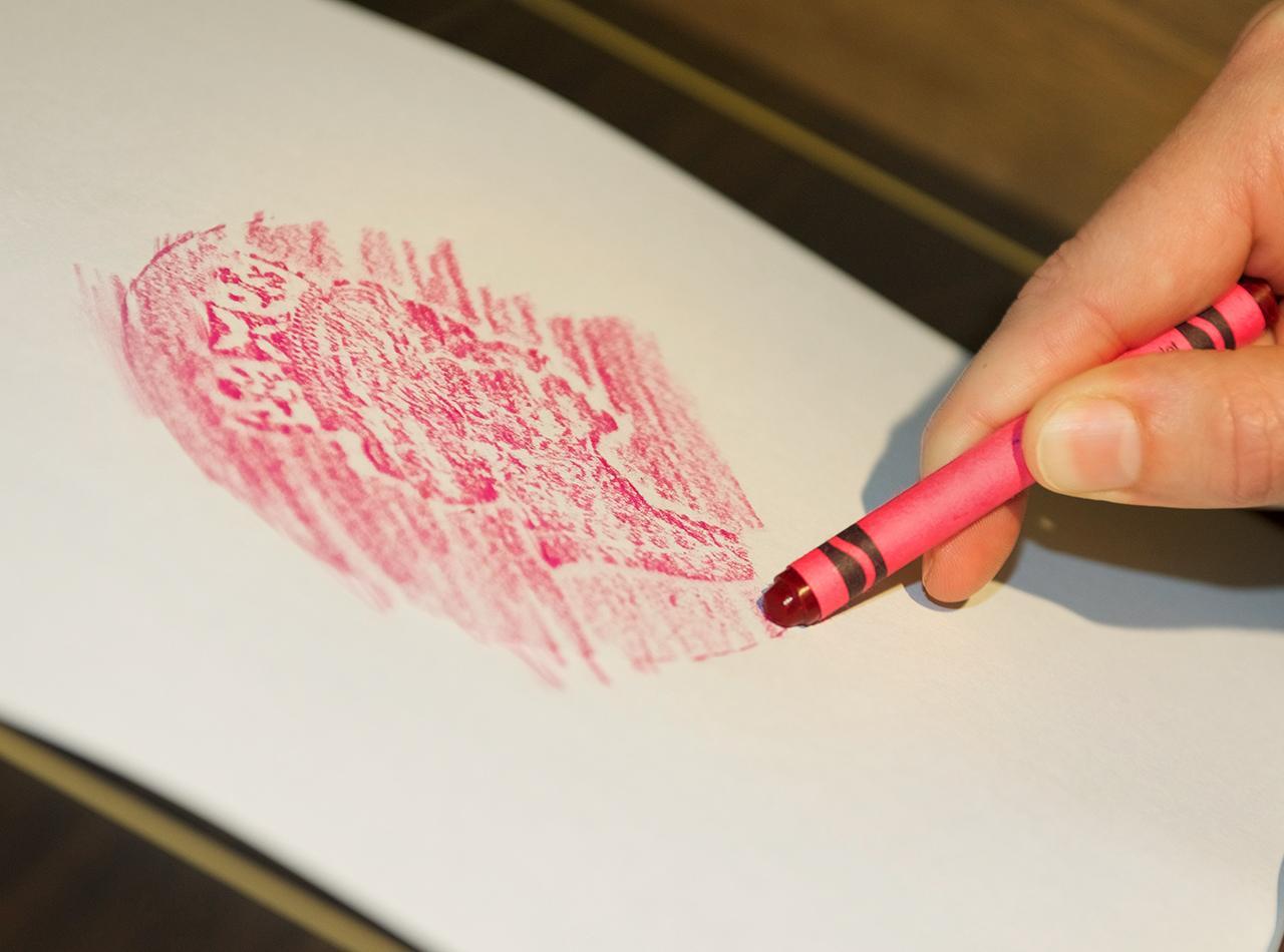 crayon frottant une pièce de monnaie géante