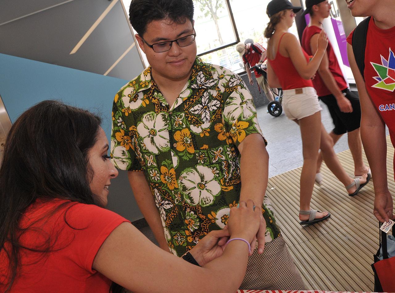 un bénévole qui applique un tatou sur un bras d'un visiteur