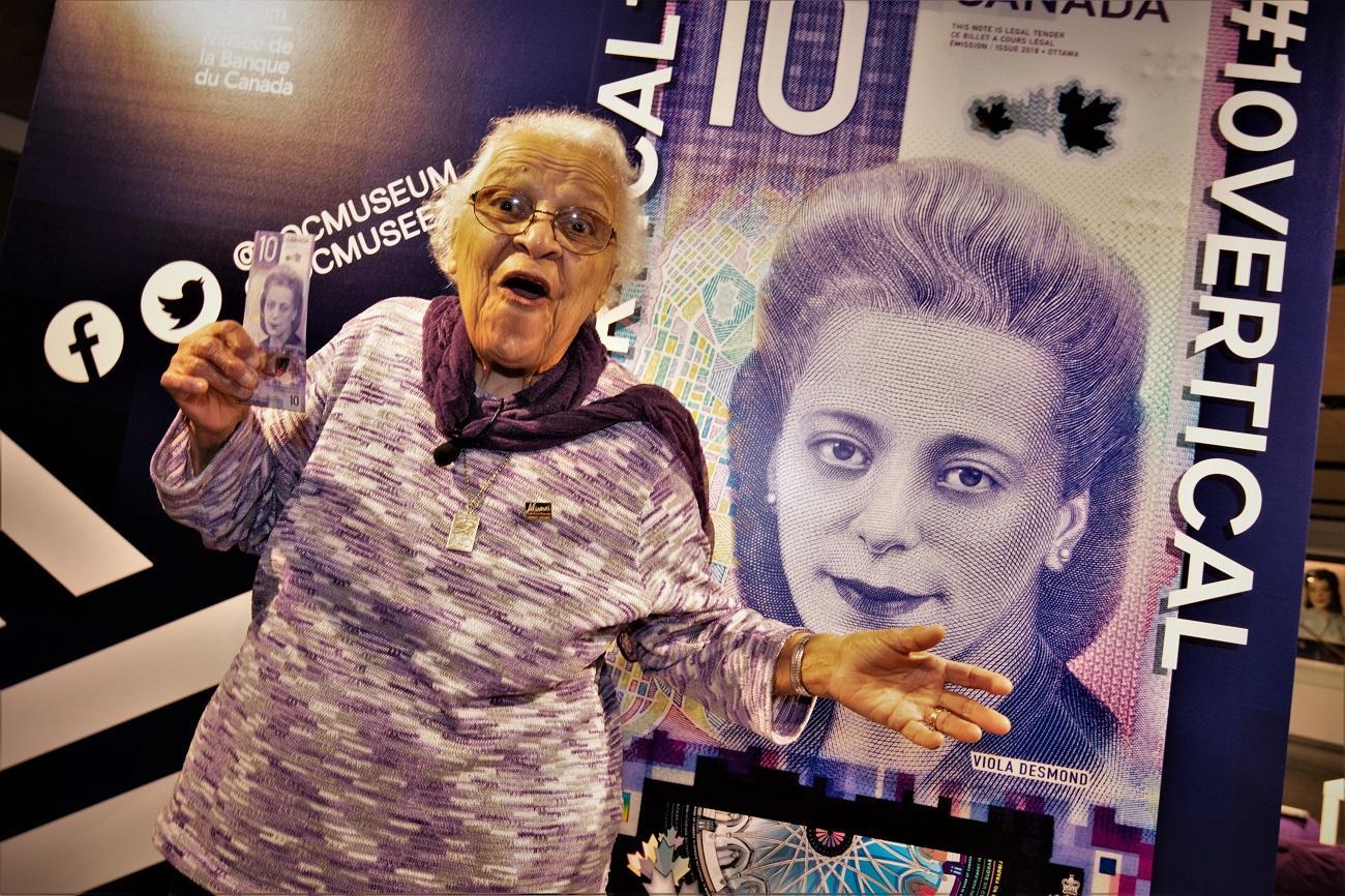 Wanda Robson tenant un nouveau billet de 10 $