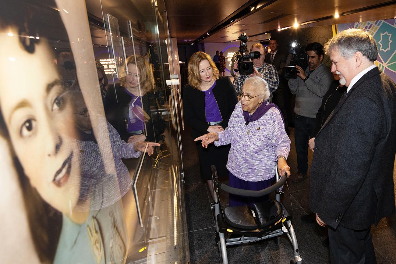 Wanda Robson regardant une photo de Viola Desmond exposée dans une vitrine de musée