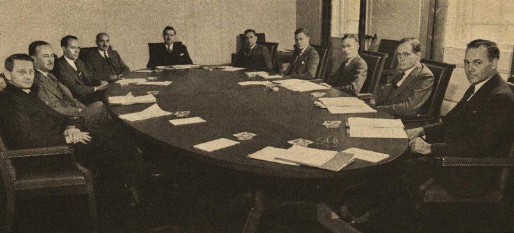 photographie en noir et blanc d'hommes autour d'une table de conseil
