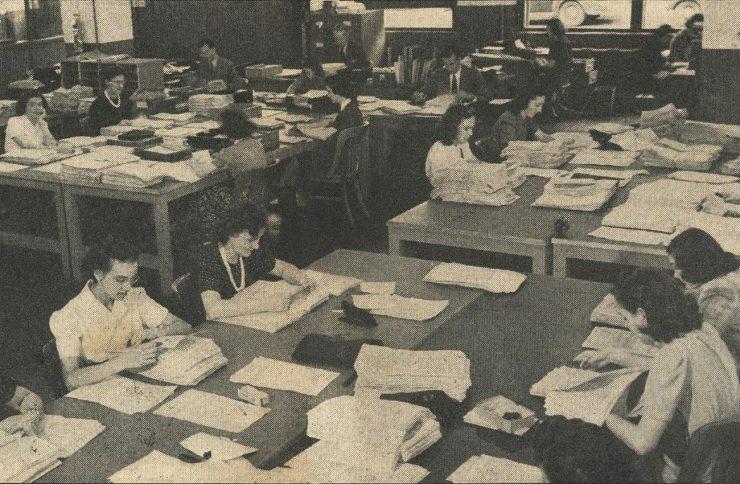 photographie tirée d'un journal montrant des douzaines de femmes au travail dans un bureau à aire ouverte