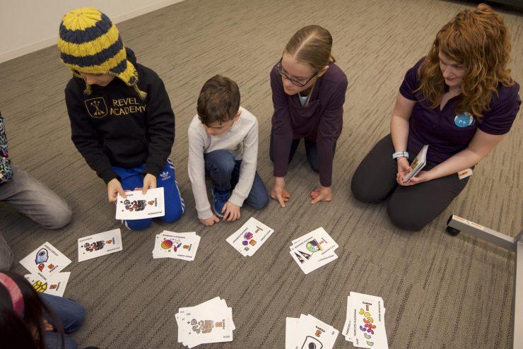 des élèves jouent avec des cartes représentant des ressources dans le cadre du programme scolaire Commerce interplanétaire