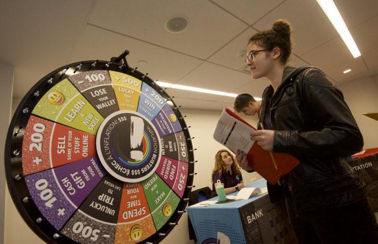 une élève fait tourner la roue chanceuse dans le cadre du programme scolaire Échec à l'inflation!