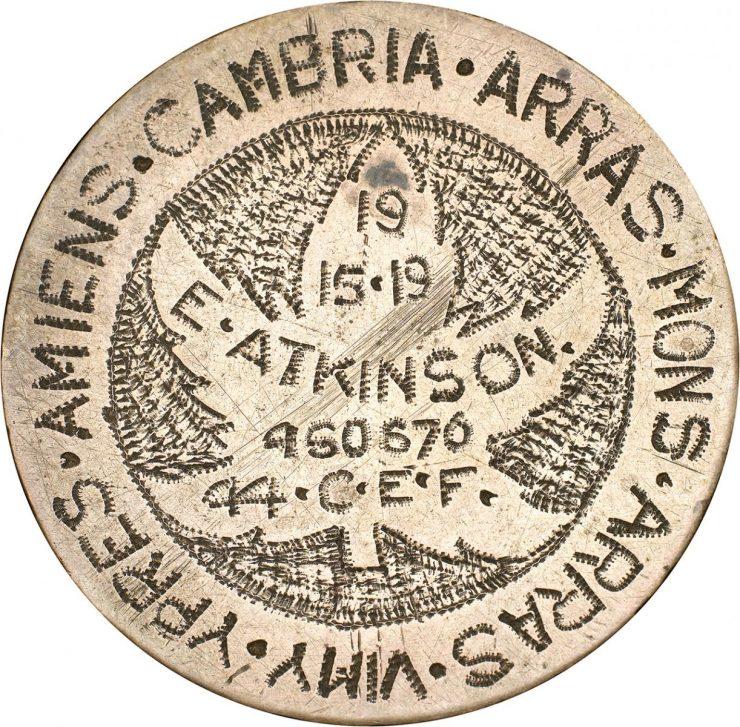 une pièce de monnaie polie où sont gravés le nom de batailles de la Première Guerre mondiale, une feuille d'érable et le nom et le matricule d'un soldat