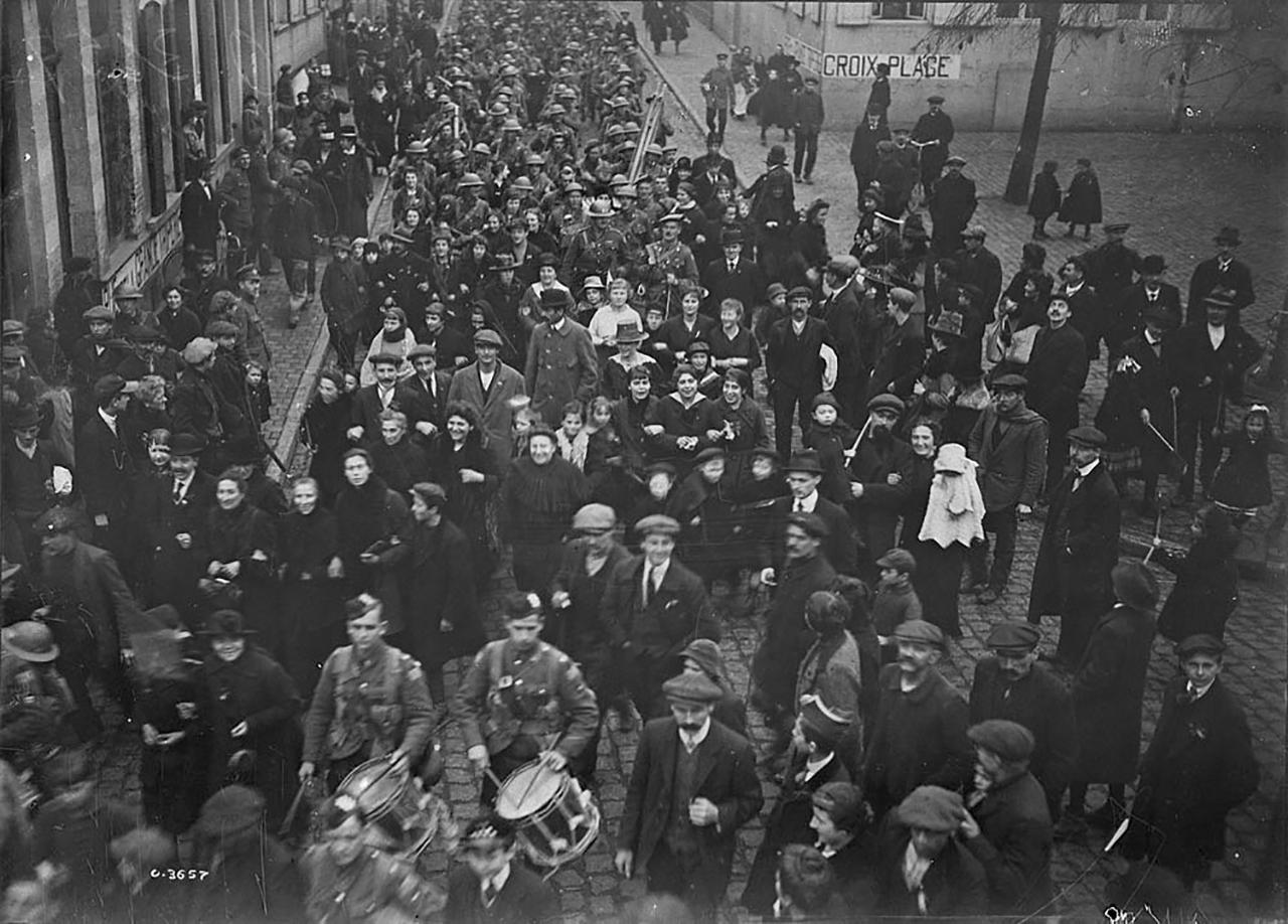 photographie d'époque montrant une foule et des soldats en marche