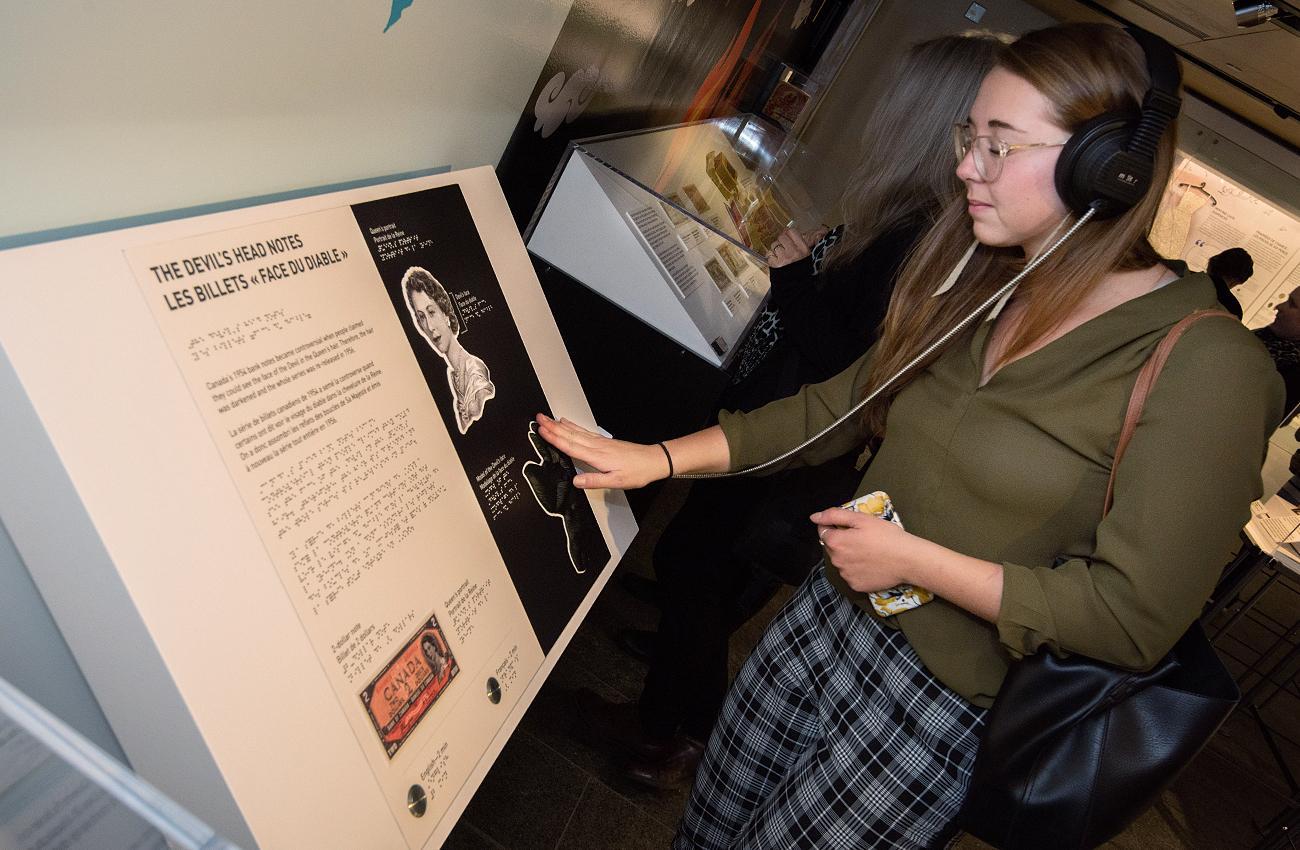 une femme touche un objet de l'exposition