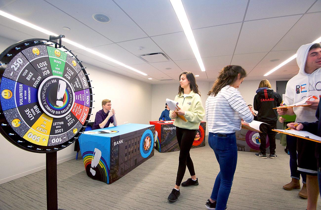 des élèves font affaire les uns avec les autres dans une salle avec des tables aux couleurs vives
