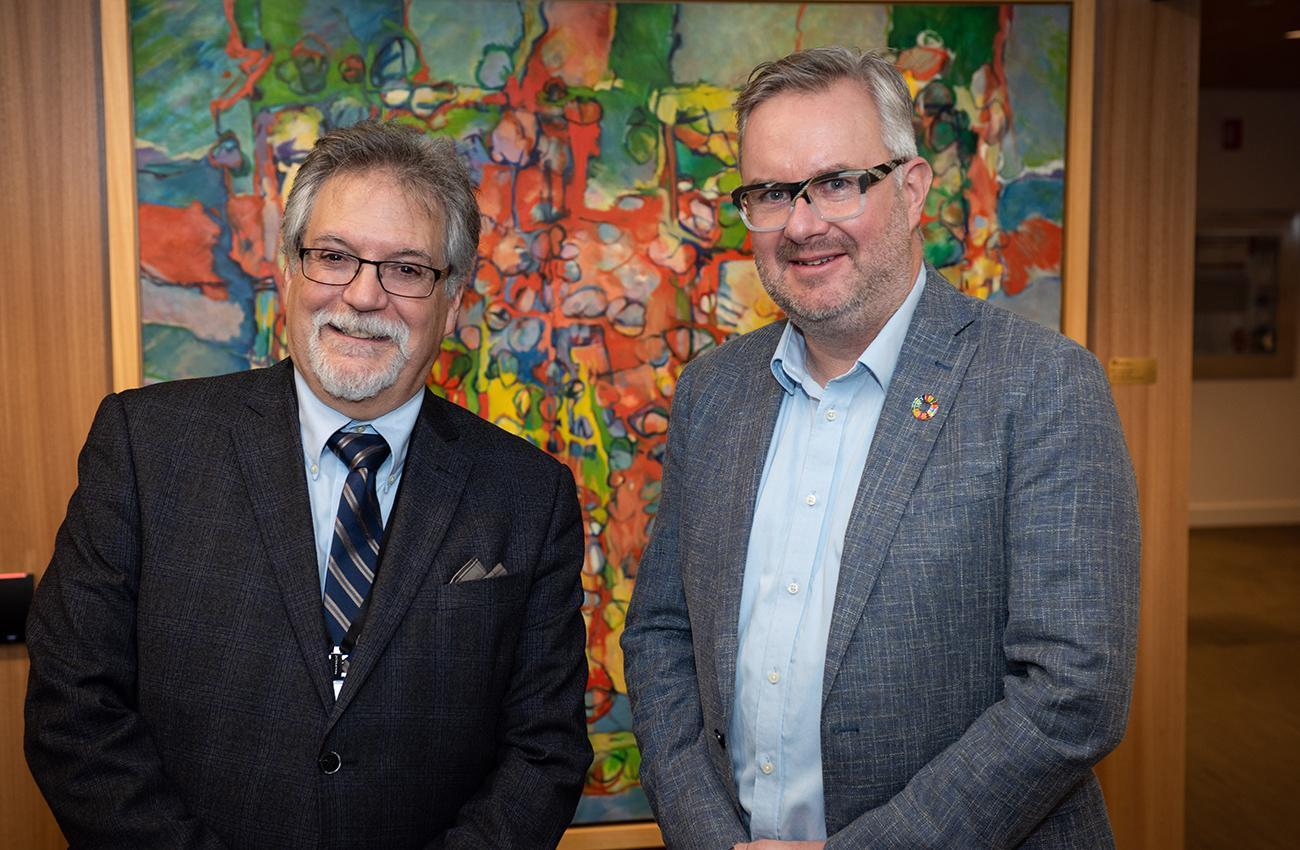 photo de deux hommes debout devant une peinture