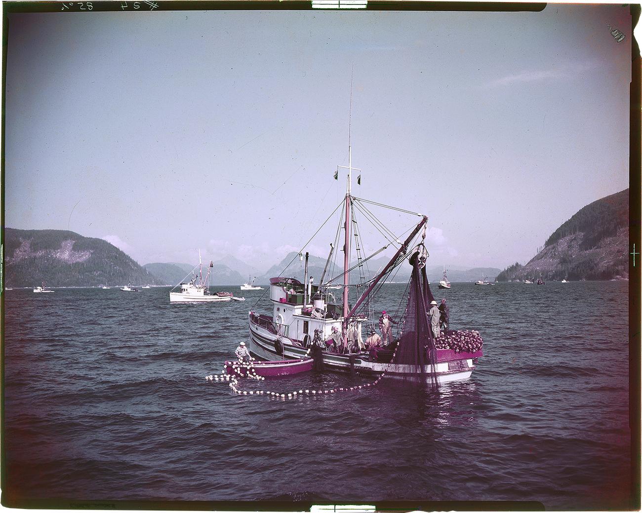 photo couleur d'un bateau de pêche sur l'océan près de montagnes