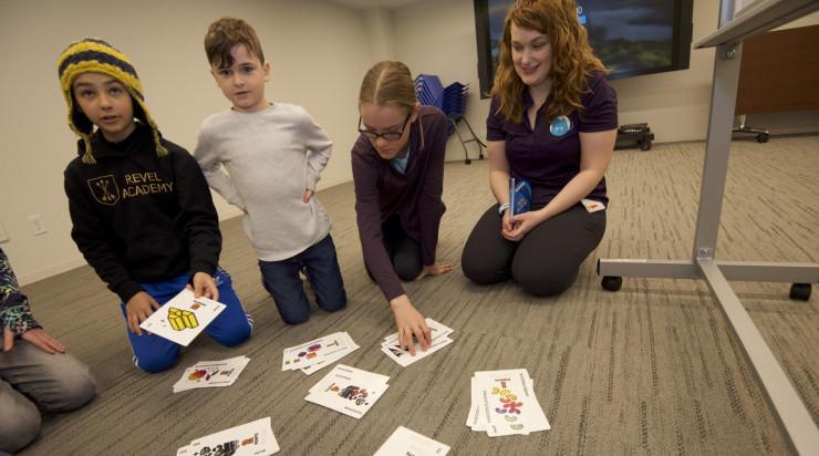 De jeunes élèves, assis par terre avec leur professeur, regardent les cartes de ressources qu'ils échangeront lors de l'activité.