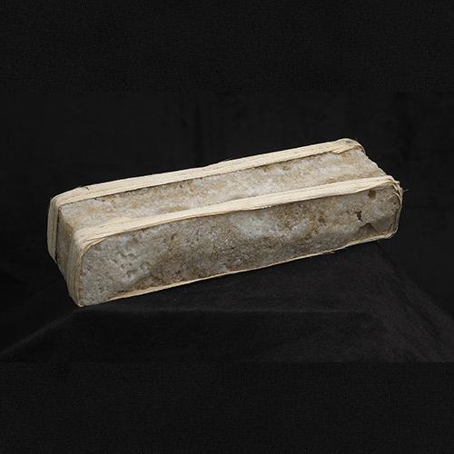 Longue brique de sel brun pâle de forme rectangulaire.