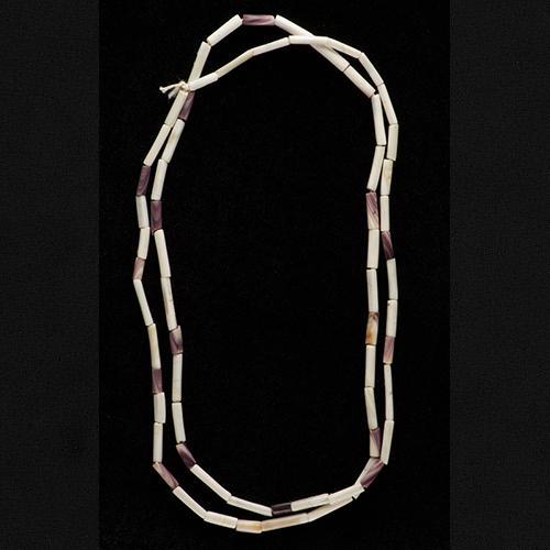 Chapelet de wampum fait de longues perles cylindriques de couleur beige, mauve ou brune. On dirait un collier!