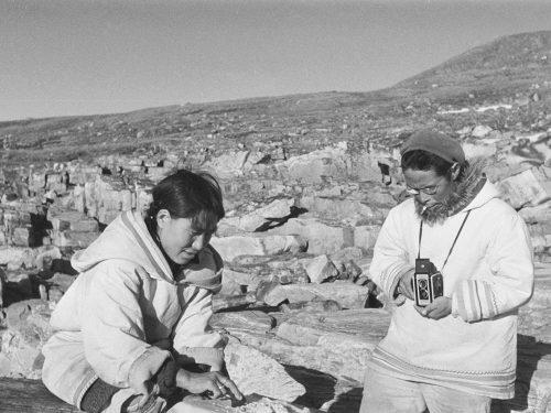 Photo en noir et blanc d'un homme inuit en train de photographier une femme qui gratte une peau.