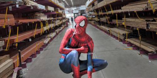 Homme habillé en superhéros accroupi dans une allée d'un centre de rénovation.