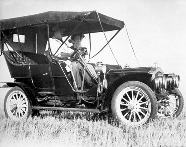 Photo en noir et blanc d'une voiture dans un champ avant la Première Guerre mondiale.