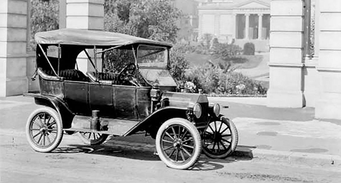 Photo historique d'une automobile stationnée devant des édifices publics avant la Première Guerre mondiale.