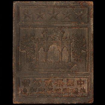 Une brique brune de forme carrée et aplatie couverte de caractères chinois