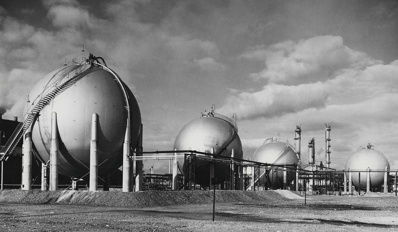 Photo en noir et blanc d'une rangée d'énormes sphères argentées devant de grandes cheminées industrielles.