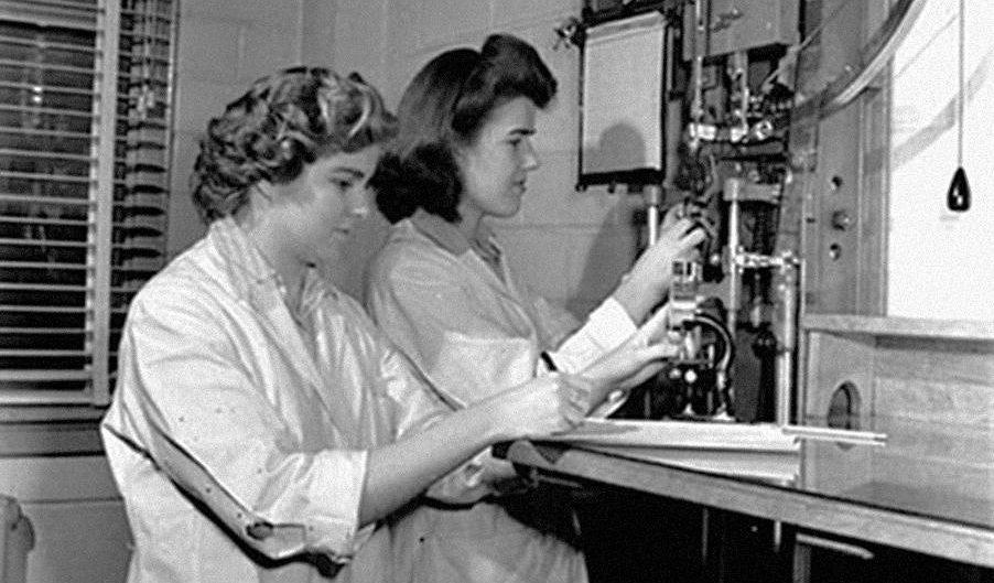 Photo en noir et blanc de deux jeunes femmes en blouse blanche dans un laboratoire.