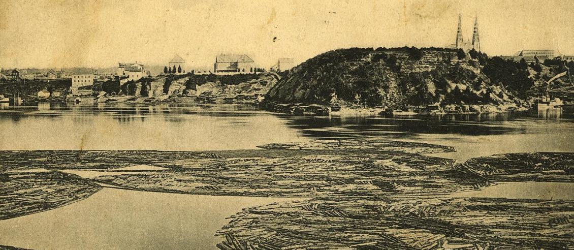 Photo en noir et blanc de billots retenus par des chaînes flottant sur une rivière devant une colline boisée.