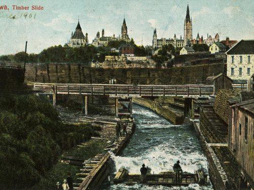 Photographie d'hommes sur un radeau de billots bien alignés le long d'un canal sur fond d'édifices gothiques.