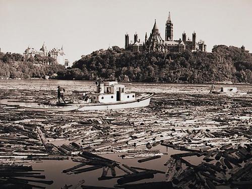 Photographie en noir et blanc de milliers de billots et de deux bateaux sur une rivière devant une colline boisée surmontée de tours gothiques.