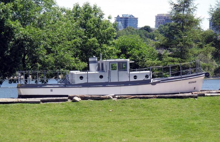 Photographie en couleurs d'un petit bateau blanc avec cabine et cheminée, exposé sur la terre ferme dans un parc.