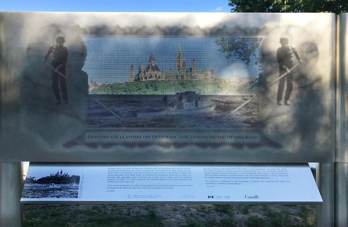 Photographie en couleurs d'un panneau en métal perforé sur lequel il y a une photo au travers de laquelle on peut voir le paysage.